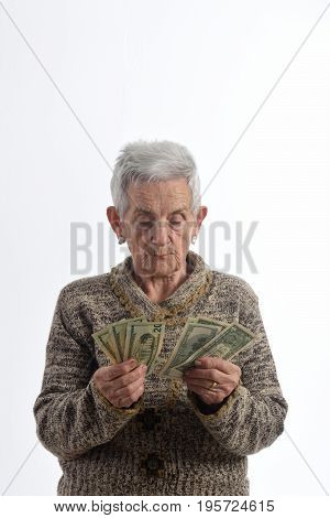 Old woman counting banknotes on white background