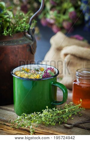 Enameled mug of healing herbs old tea kettle honey jar and medicinal plants for healthy herbal tea. Herbal medicine.