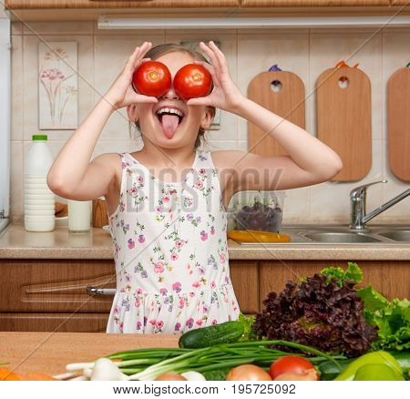 child girl having fun with tomatoes, look through like binoculars, fruits and vegetables in home kitchen interior, healthy food concept