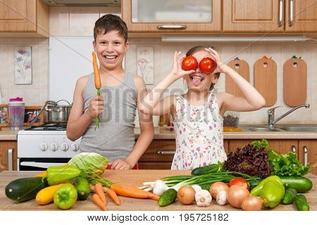Child girl and boy having fun with tomatoes and carrot, look through like binoculars. Home kitchen interior with fruits and vegetables. Healthy food concept