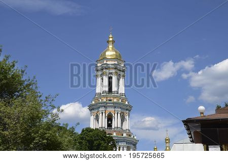 Beautiful bell tower with a golden dome and a cross an Orthodox monastery against a blue sky