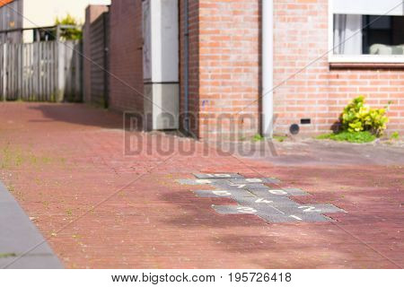Hopscotch childrens game drawn with chalk on pavement playground with figures and numbers red house behind