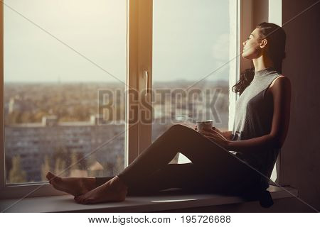 Resting and thinking woman with closed eyes. Calm girl with cup of tea or coffee sitting on the window-sill at home. Side view. Young attractive multi-racial Asian Caucasian lady in casual clothes resting indoors
