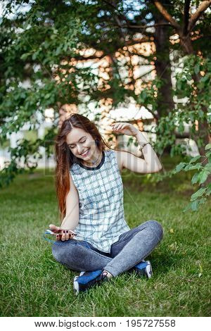 Portrait of beautiful white Caucasian woman with long red hair in jeans and plaid shirt sitting on grass outside in park. Woman with earbuds earphones listening to music on her phone on Internet.