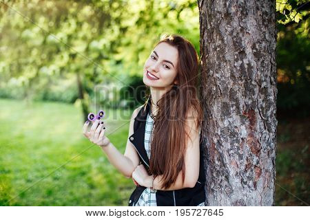 Portrait of smiling white Caucasian young beautiful woman with long hair and brown eyes playing with fidget spinner toy. Girl holding fidget spinner for stress relief.