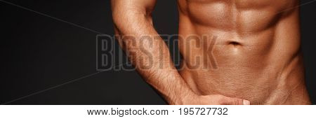 Sexy closeup portrait of handsome topless male model with beautiful eyes. Sexy man or muscular macho, bodybuilder, with muscle torso, body with six packs and abs poses on black background 16 in 9 crop for design.
