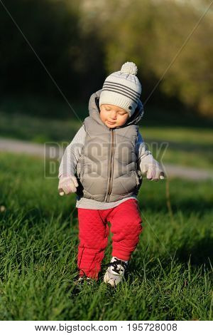 Portrait of toddler child in warm vest jacket outdoors. One year old baby boy wearing vest jacket at park meadow.
