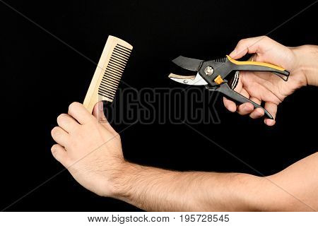 Extraordinary Barber. Male Hands Holding Shears And Comb Isolated On Black Background From Right Sid