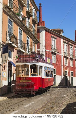 Classic red tram bus in Alfama district of Lisbon Portugal