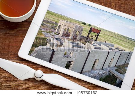 concrete ruins of one of five reduction plants and pump stations manufacturing potash during World War I near Antioch, Nebraska, reviewing aerial image on digital tablet