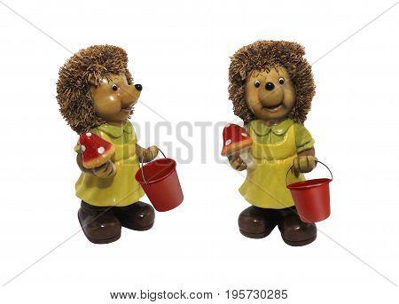 Hedgehog with bucket and mushroom. Isolated cheerful hedgehog holding an amanita mushroom and red bucket ceramic statuette.