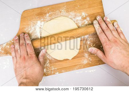 Man hands rolled dough with a rolling pin on the board