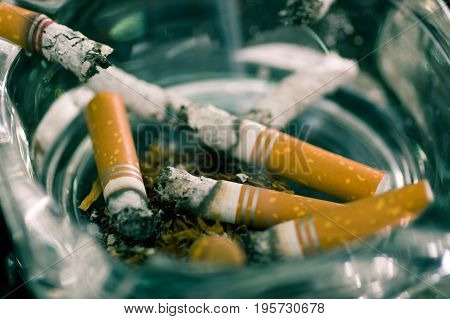 Close up of consumed cigarettes over a crystal ashtray.