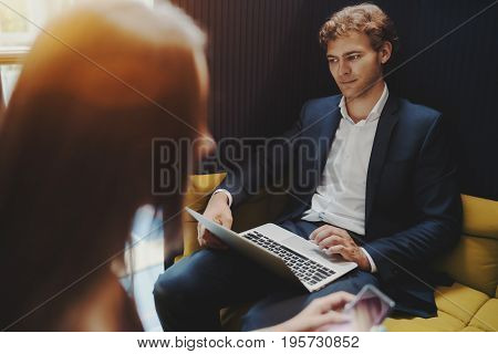 Portrait of young successful bearded boss with laptop having work business meeting blurred silhouette of his female colleague in foreground they sitting on yellow sofas in chillout office zone