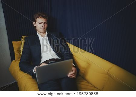Handsome businessman with short beard is leaning on yellow sofa in office chillout zone and having video conversation with his family during lunch time at his work