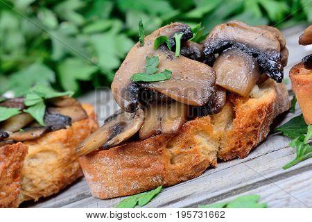 Heap of bruschetta with mushroom garlic and parsley on table