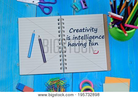 Creativity is intelligence having fun text on notebook page