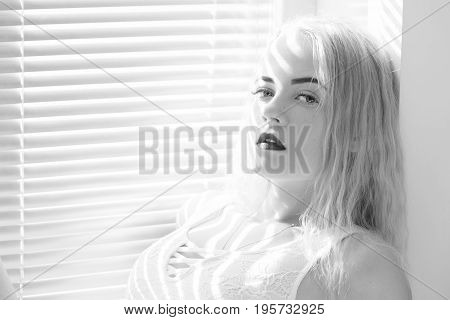 sensual girl sitting on window with blinds in sunlight, monochrome