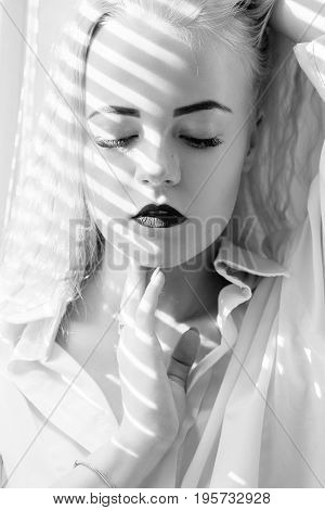 sad girl sitting on window in sunlight with blinds, monochrome