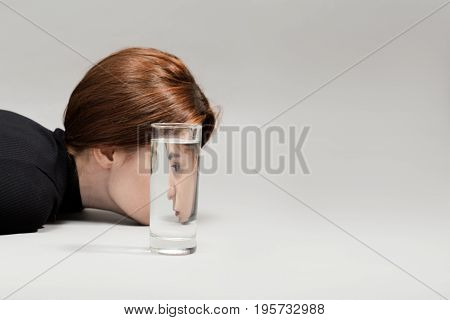sad girl profile and glass with water on gray background with copy space