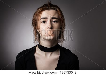 sad girl with plaster on her mouth looking at camera at gray background