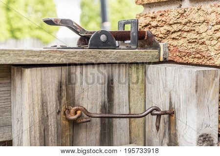 Old ineffective rusty latches on wooden gate to backyard closeup security concept