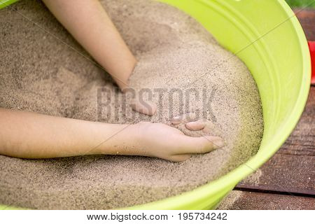 Closeup of hands enjoying and playing with cool beach sand in a bucket on a picnic table fun outdoor activity therapy and mindfulness concepts
