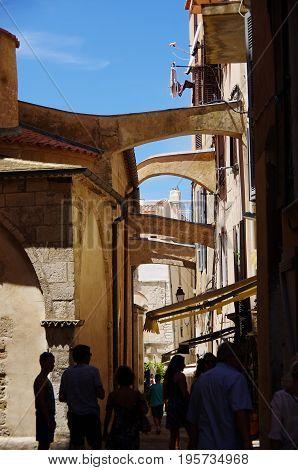 Tourists Walk In The Narrow Streets Of Bonifacio.
