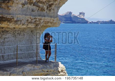 Young Female Tourist Walking And Taking Photographs Along The White Cliffs Of Bonifacio.