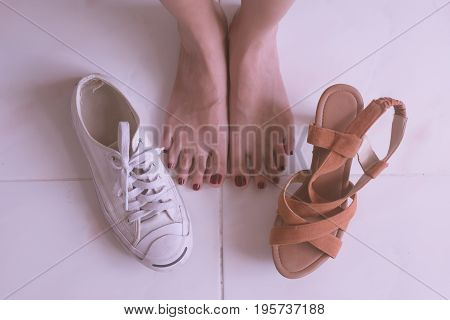 Close up of female feet with high heels shoes and casual sports shoes.