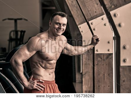 Portrait of happy smiling sporty man posing in fitness club, the image was toned