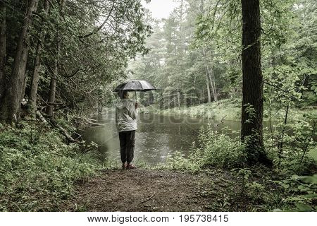 Woman with umbrella standing on a river bank in the rain