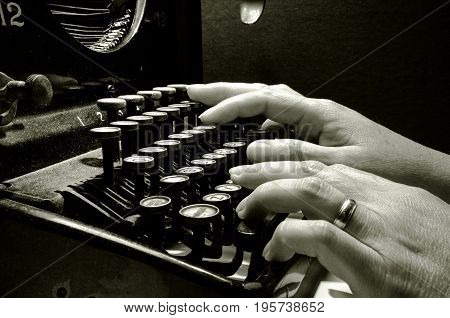 Hands typing on old typewriter keyboard B&W image