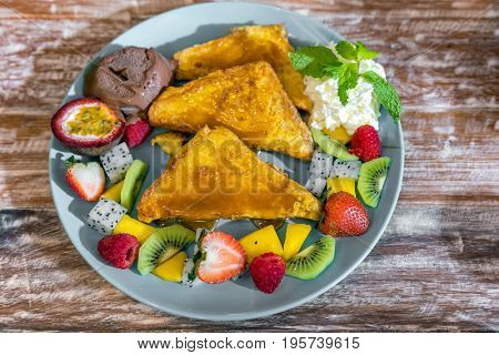 French toast served with exotic tropical fruit with ice cream gelato
