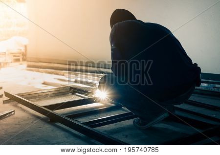 worker welding steel in dark room factory