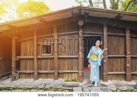Beauty girl wearing traditional kimono in front of old wooden house. Japaneses enjoying sunshine after rain asian woman looking up at clearing sky checking if it's raining during traveling on japan