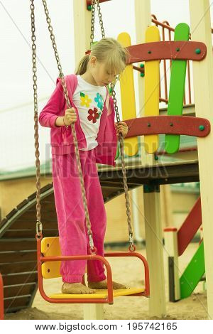 The girl in the red suit riding on a swing. A children's Playground on the beach.