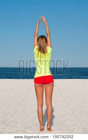 Fitness Woman Doing Exercise On The Beach.