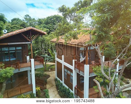 Vacation in nature resort. Aerial view on hotel villas in jungle trees around