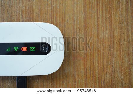 white pocket wifi with red low battery button is charging on old brown wood table background and copy space for create new idea