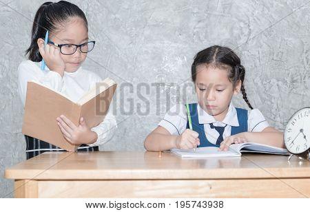 little teacher looking student doing homework in classroom education concept