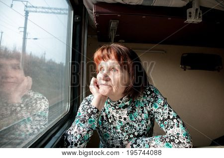 Elderly woman in a train looks out the window
