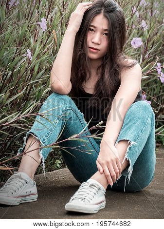 Portrait image of sexy teenager girl in flower garden. Fashion sexy woman in tank-top jeans and sneakers