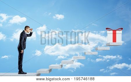 A businessman on sky background looking up at a grey stairway to see a white giftbox with a red bow. Winner's reward. Job bonus. Corporate present.