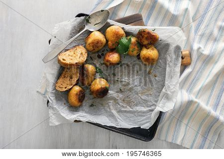 New baked potatoes on a baking sheet on white rustic wooden table top view