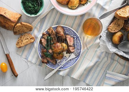 Plate with steak grilled and new fried potatoes on a light wooden table with brandy top view. Dinner table concept