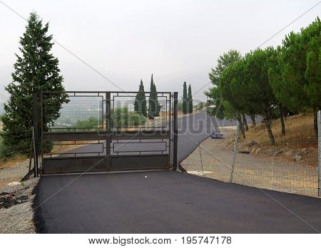 Steel Gate and tarmacked road in Andalusian village
