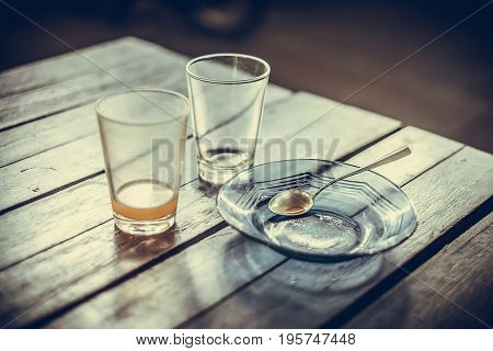 Empty Glass Of Hot Tea In With Saucer And Spoon On Wooden Table Vintage Tone, Shallow Focus.