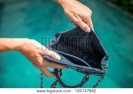 Woman hands opening empty luxury snakeskin python handbag