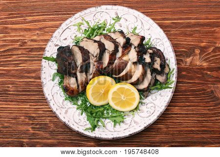 Roast fillet leg of lamb with greens and lemon on a wooden table